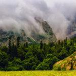 Панорама, вид на гору Фишт закрытую облаками и скалу Фиштенок